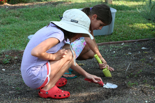Girls planting seeds in the garden